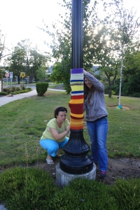 Sherry helping Lisa install her yarnbomb piece on a lamp post.